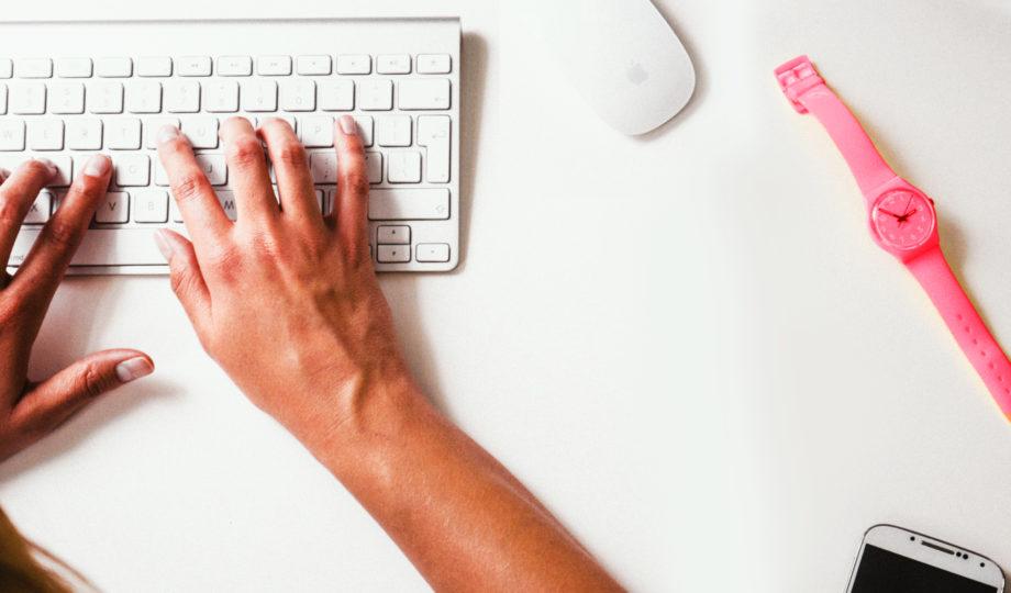 Marketing de conteúdo: pessoa escrevendo um texto usando teclado wireless em cima de uma mesa branca
