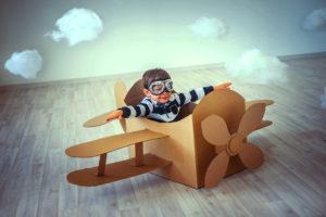 Criança voando em caixa de papelão